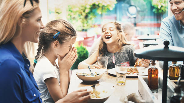 Young family having lunch at a restaurant. - foto stock