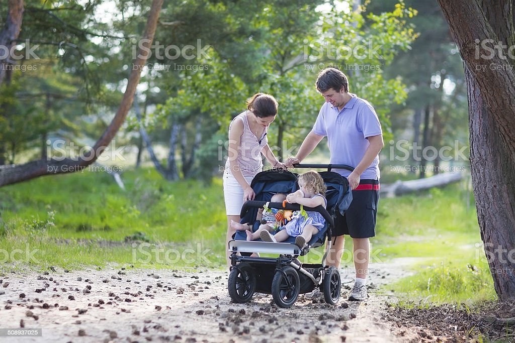 Young family hiking with two kids in a stroller royalty-free stock photo