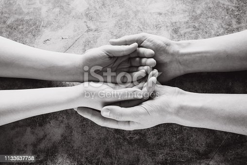 974882202istockphoto Young family holding hands offering help, protection and support symbol. Sharing hope concept 1133637758