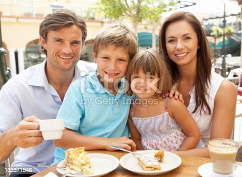 Young Family Enjoying Cup Of Coffee And Cake In Cafe