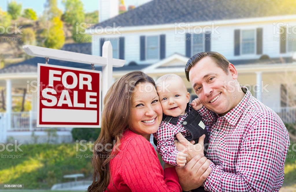 Young Family In Front of For Sale Sign and House stock photo