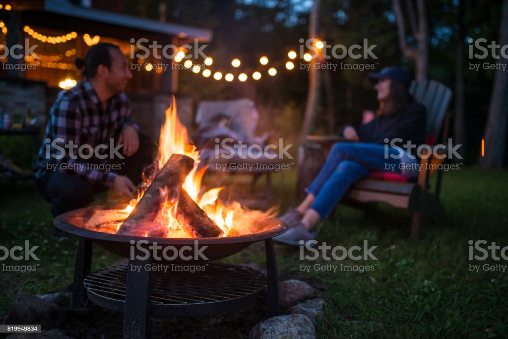 Young family is warming near campfire late evening at a beatiful canadian chalet stock photo