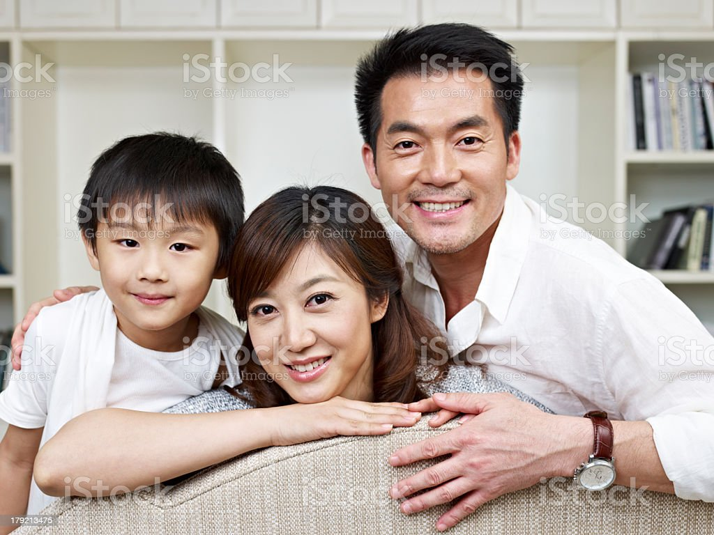 Young family leaning over back of couch and smiling royalty-free stock photo