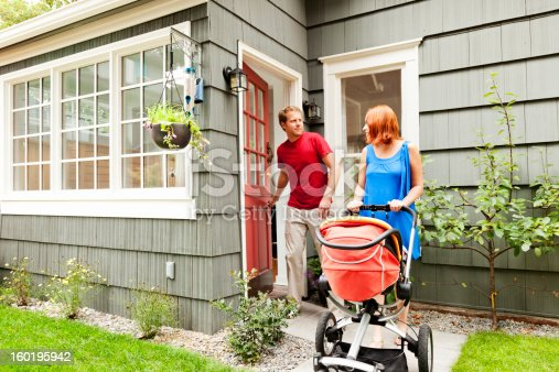 Photo of a young family on their way out to take a walk with their new baby in a stroller; husband is shutting the door behind him.