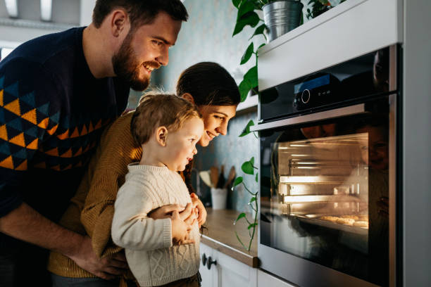Young family looking at the oven stock photo