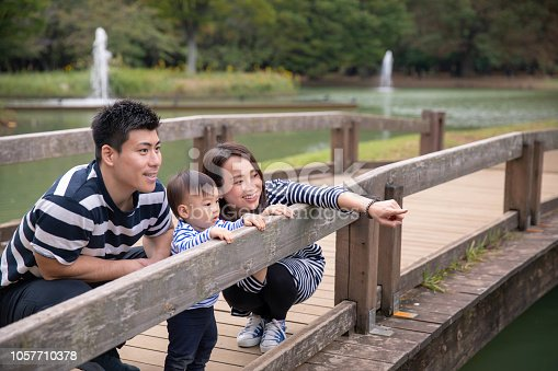 Young family looking at the same direction from wooden bridge in public park