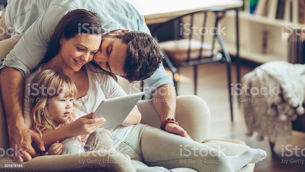 Young family looking digital tablet stock photo