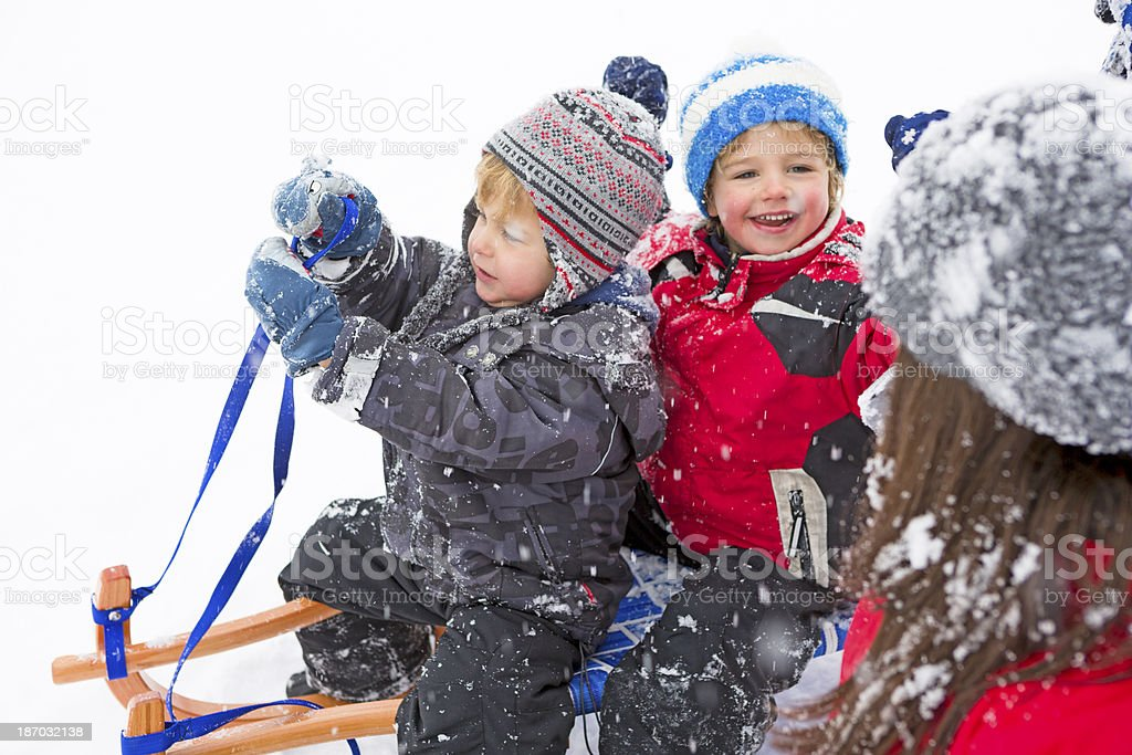 Young family making a trip with the sleigh royalty-free stock photo