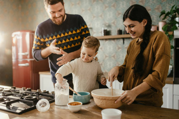 Young family making dough for cookies stock photo