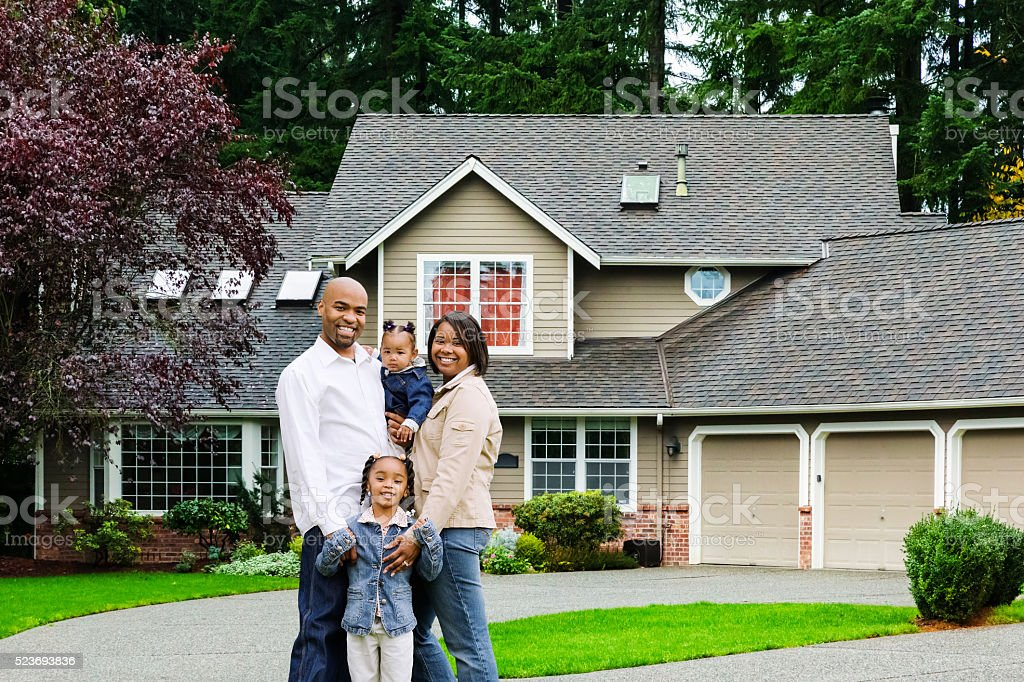 Young Family of Four at Home Photo of a happy African American family of four standing in front of their home. 25-29 Years Stock Photo