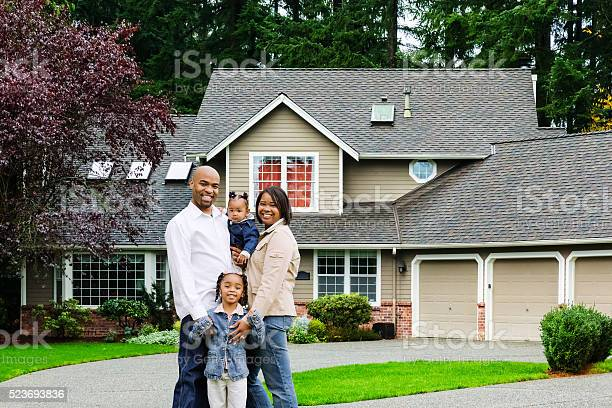Young Family Of Four At Home Stock Photo - Download Image Now
