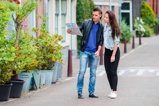 junge familie mit zwei mit karte in europäischen stadt, amsterdam, niederlande - hochzeitsreise amsterdam stock-fotos und bilder