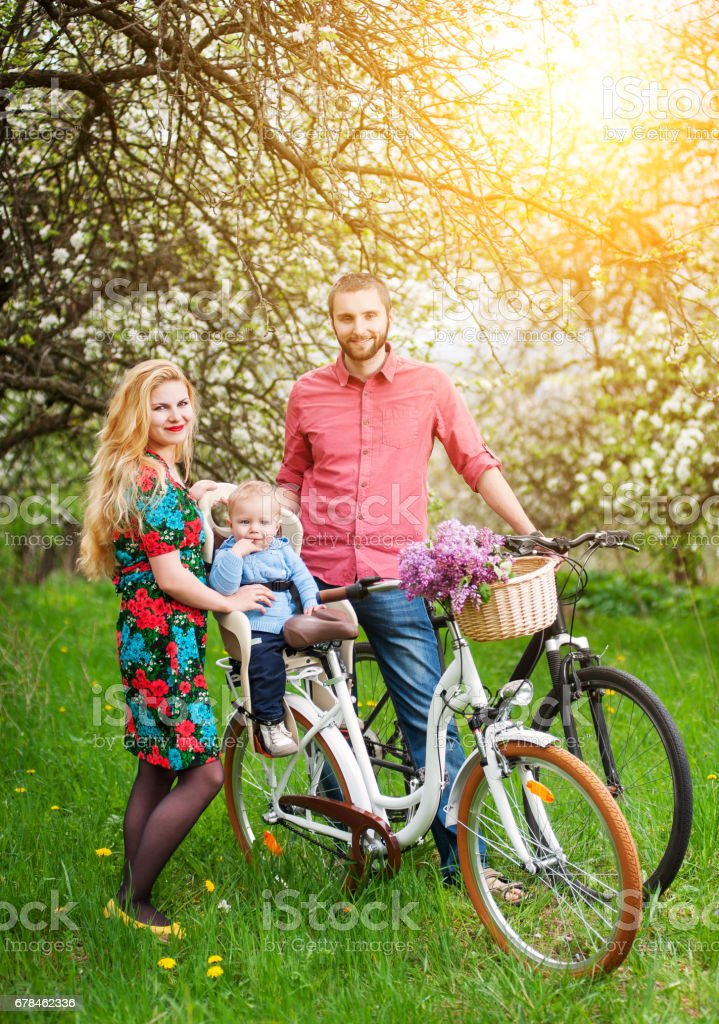 Young family on a bicycles in the spring garden royalty-free stock photo
