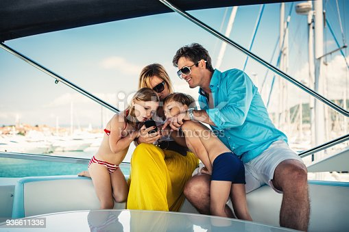 Young family using mobile phone on the yacht.