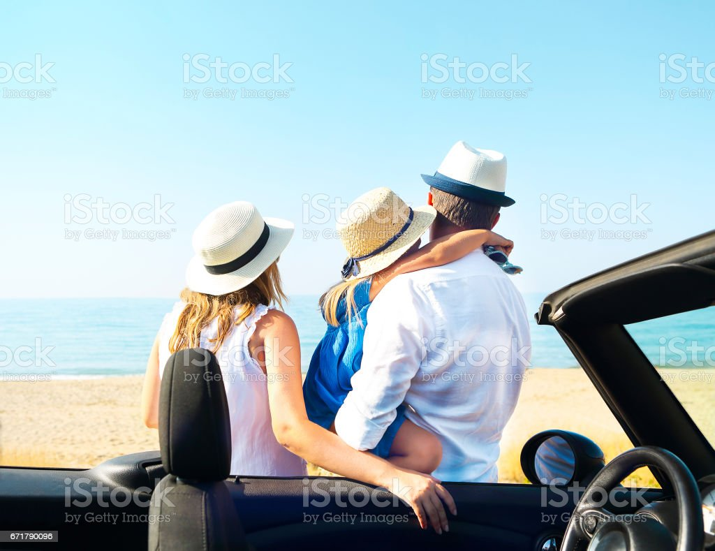 Young family on the beach. Travel and summer vacation concept stock photo