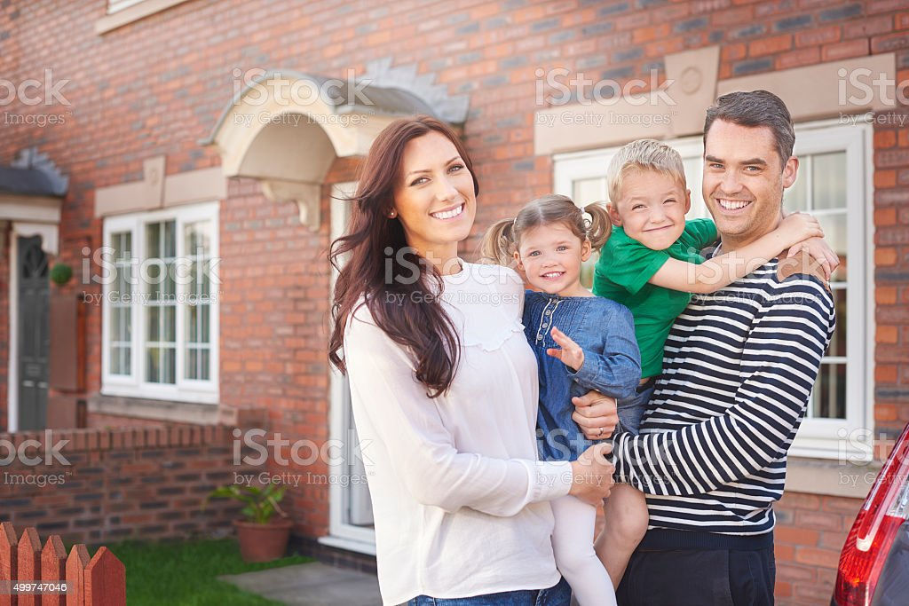 young family outside their home stock photo