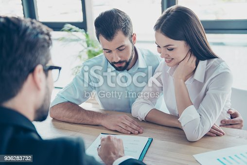 istock Young family, partners are making a deal with lawyer about their start up. Men is reading contract carefully to be ready to sign it, all are well dressed, focused, lady is smiling 936283732