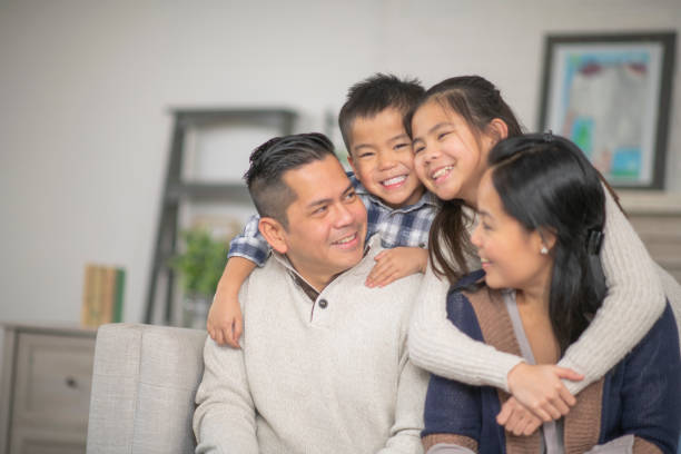Young Family A family of four are embracing in their living room one afternoon. Everyone is smiling happily. filipino ethnicity stock pictures, royalty-free photos & images