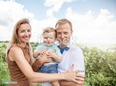 happy young couple with a toddler boy, outdoor portrait