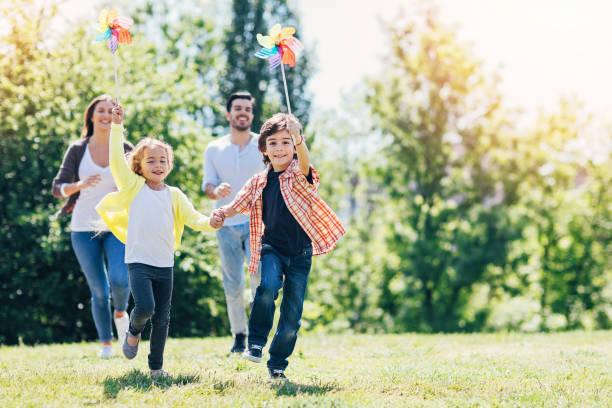 junge familie spielen im park - ferienpark stock-fotos und bilder