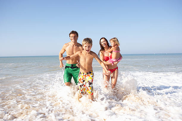 Young family playing on beach stock photo