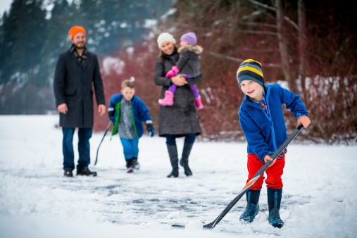 Young family playing pond hockey outside in the snow.