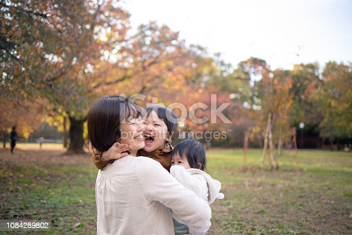 Young family playing together in public park