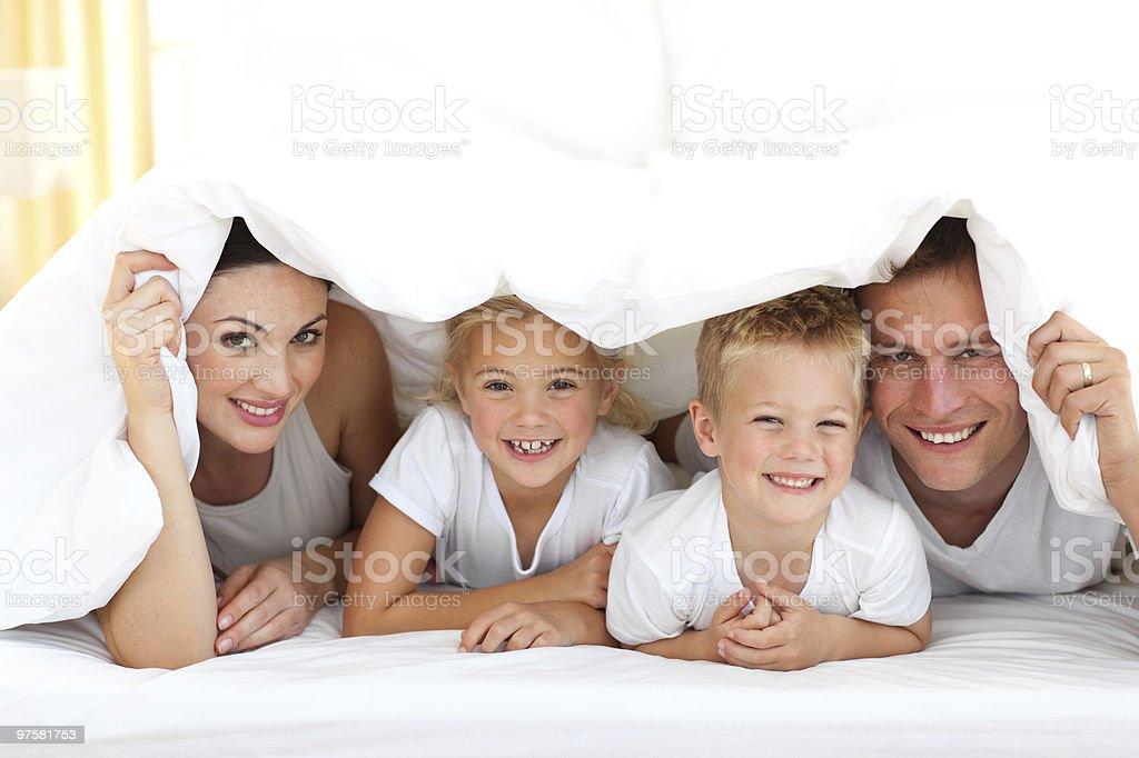 Jeune famille jouer ensemble sur un lit photo libre de droits