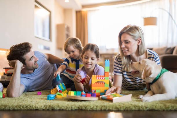 Young family playing with toy blocks on carpet in the living room picture id958687794?b=1&k=6&m=958687794&s=612x612&w=0&h=utvloz0fhrekmmtsu6xfr gyyunrrhlvk4tc6mhkisi=
