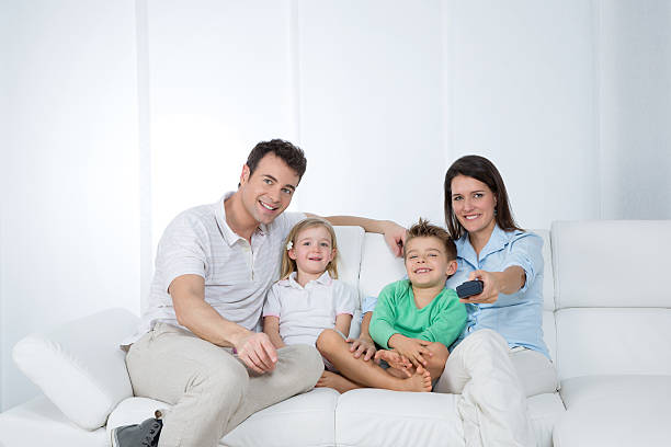 young family posing on sofa stock photo