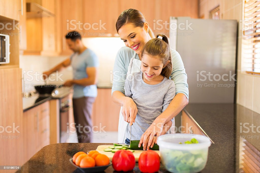 young family preparing meal in kitchen stock photo