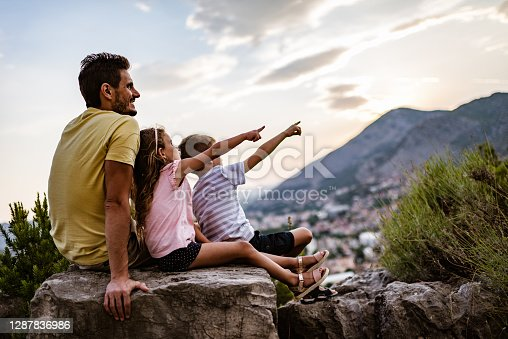 Single father and his children relaxing in mountains at sunset.