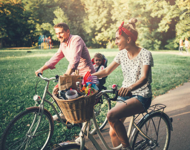 Young family riding bicycles in the park - foto stock