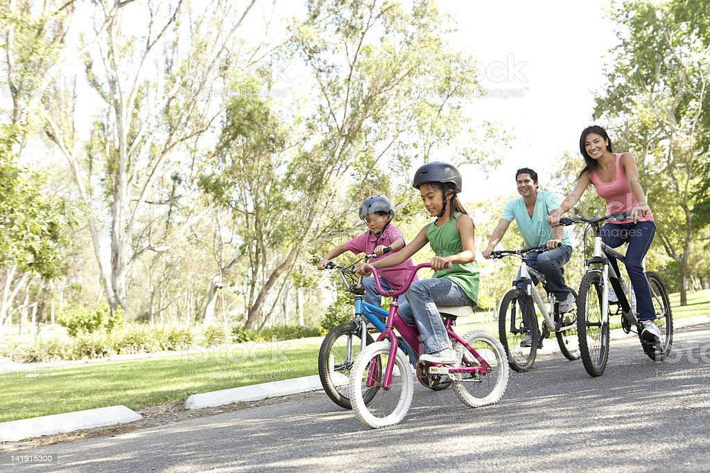 Young Family Riding Bikes In Park stock photo