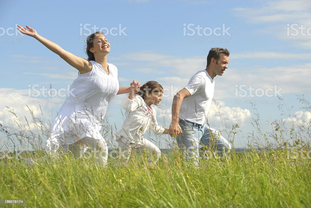 Young family running on meadow royalty-free stock photo
