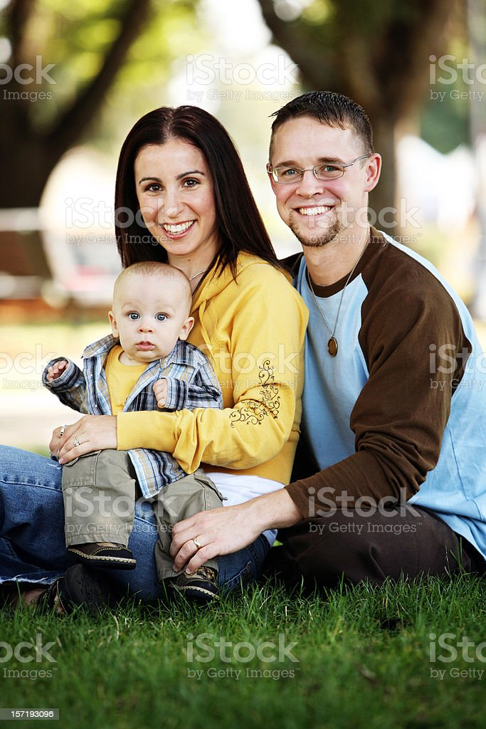 Young Family Sitting in Park Holding Their Child royalty-free stock photo