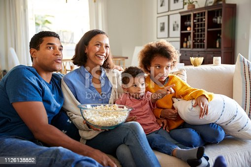 istock Young family sitting together on the sofa in their living room watching TV and eating popcorn 1126138852