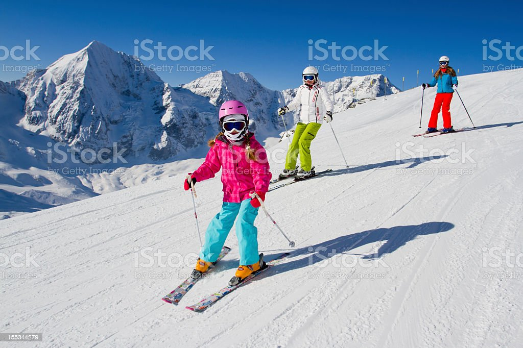 Young family skiing down a snowy slope stock photo