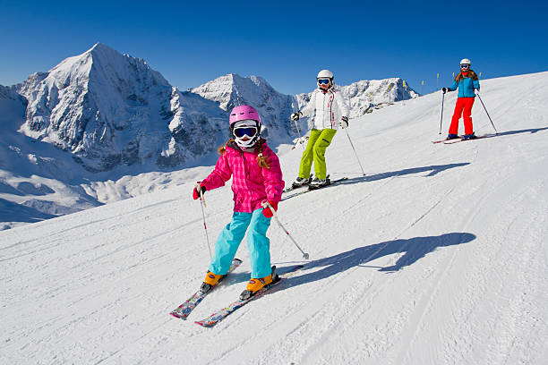 Young family skiing down a snowy slope Skiing, winter, ski lesson - skiers on ski slope ski stock pictures, royalty-free photos & images