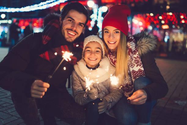 junge familie verbringen weihnachten außerhalb - weihnachten 7 jährige stock-fotos und bilder