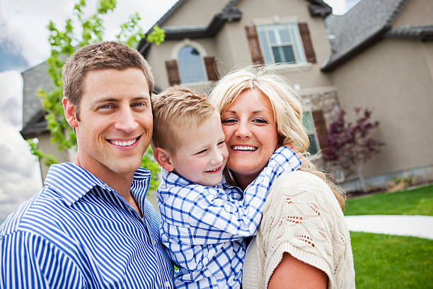 A young family standing in front of their new home stock photo