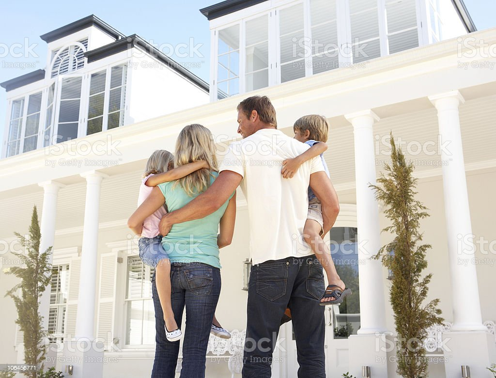 A young family stands outside of a gorgeous dream home royalty-free stock photo