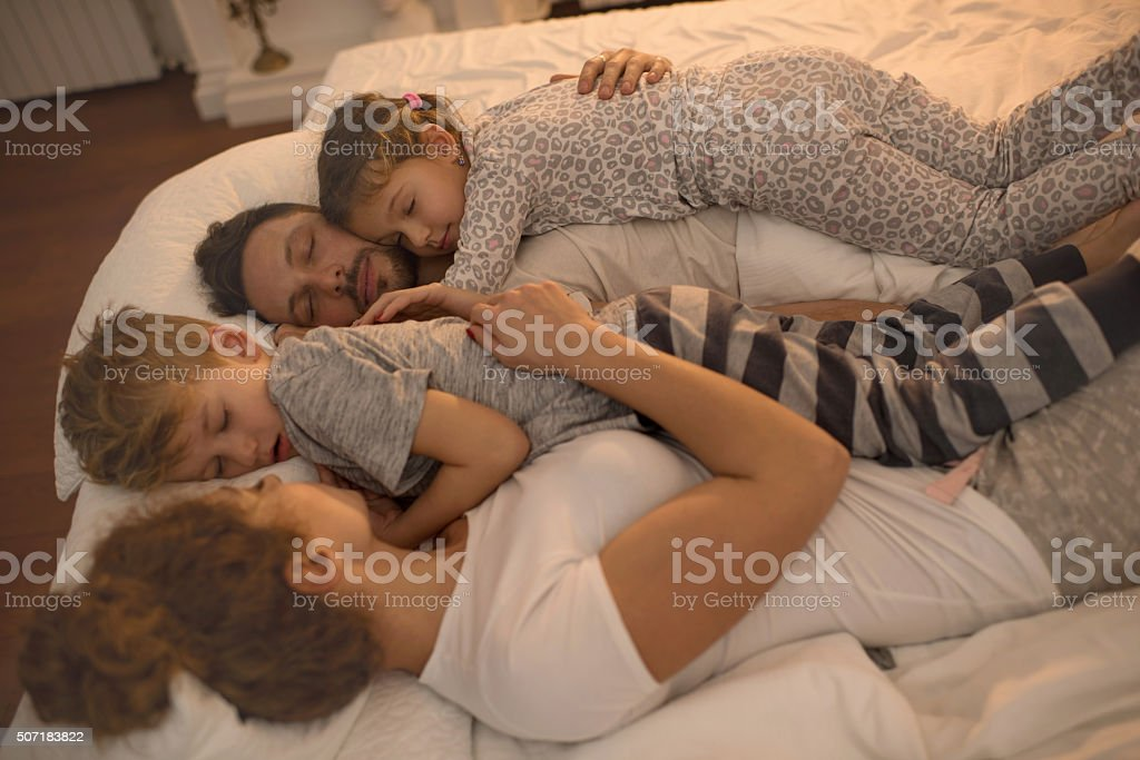 Young family taking a nap together on a bed. stock photo