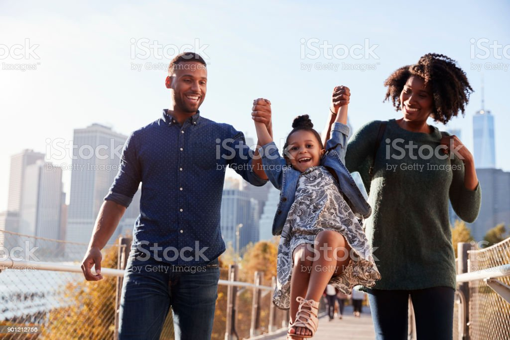 Young family taking a walk on footbridge, close up stock photo
