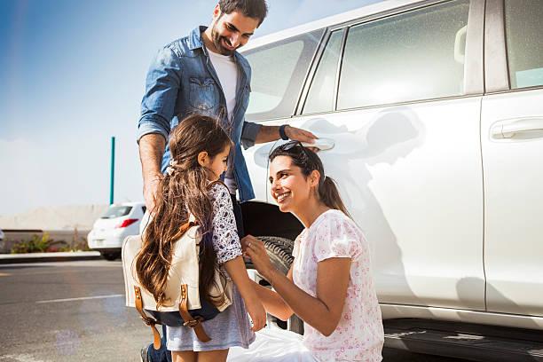 jeune famille prenant sa fille à l'école en voiture - jeunes arabes photos et images de collection