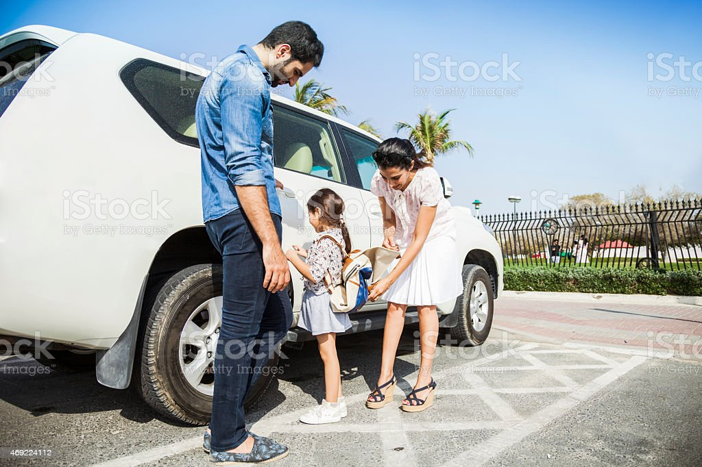 Young family taking daughter to school by car stock photo