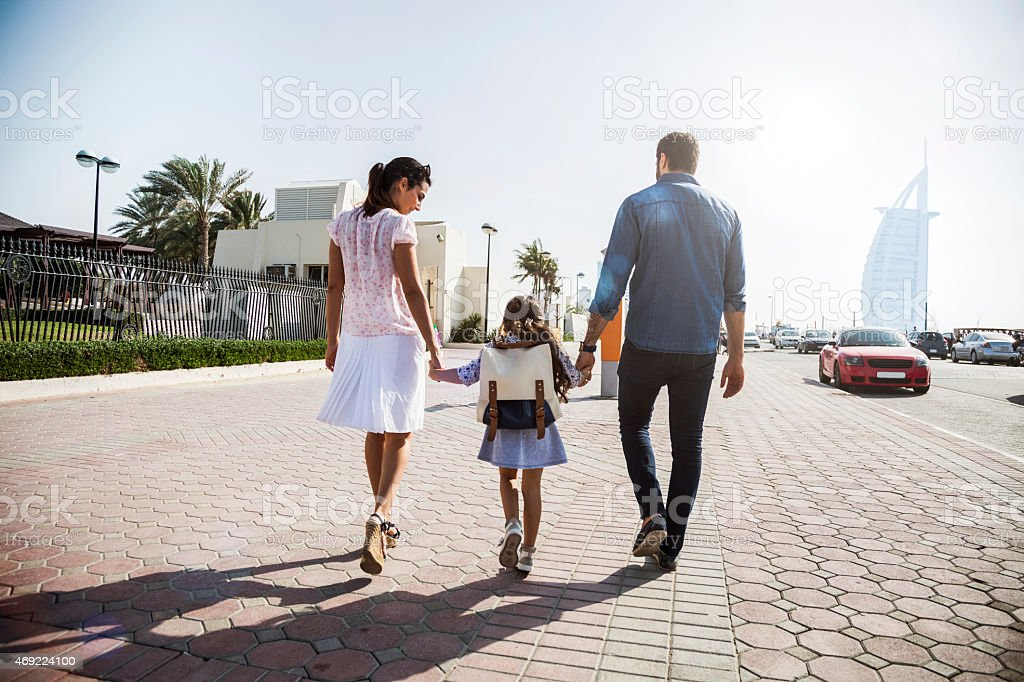 Young family in Dubai - UAE, taking their little girl to school in...