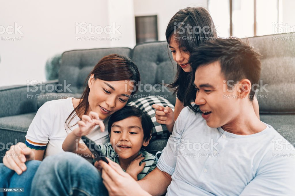 Young family texting at home stock photo