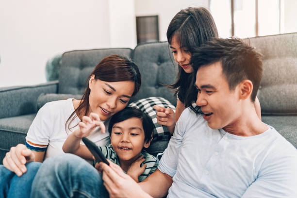 Young family texting at home Asian ethnicity family with two children and smart phone at home southeast asia stock pictures, royalty-free photos & images