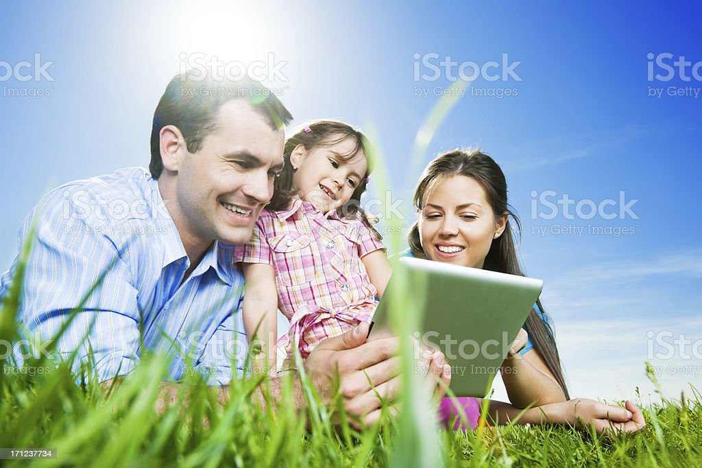Young family using a digital tablet in the park. royalty-free stock photo